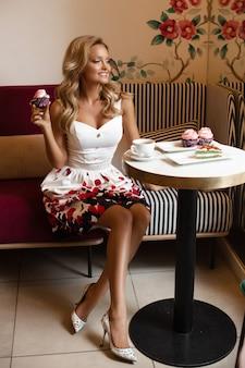 Hermosa dama en vestido de verano tomando café en la cafetería.
