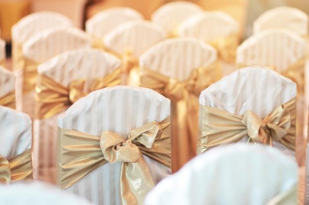 Hermosa decoración de sillas con cinta en salón de eventos de bodas.