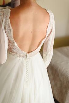 Hermosa y delgada novia de vuelta con su vestido en el día de su boda