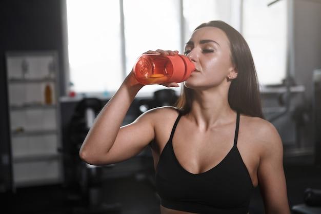 Hermosa deportista bebiendo agua después de hacer ejercicio