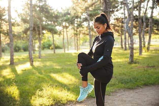 Hermosa deportista en forma haciendo ejercicios de calentamiento antes de trotar en el parque, escuchando música con auriculares