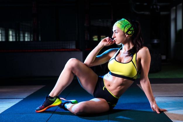 Hermosa, deportiva niña está sentada en el gimnasio. fondo oscuro vestido con pantalones cortos y una camiseta con un vendaje en la cabeza.
