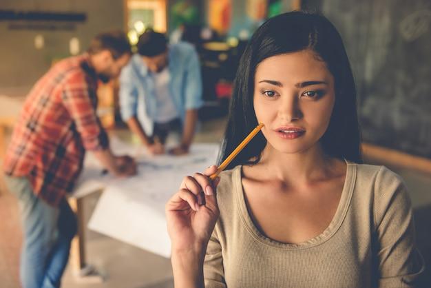 Hermosa diseñadora en ropa casual está sosteniendo un lápiz