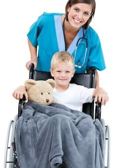Hermosa doctora llevando adorable niño pequeño en el whee