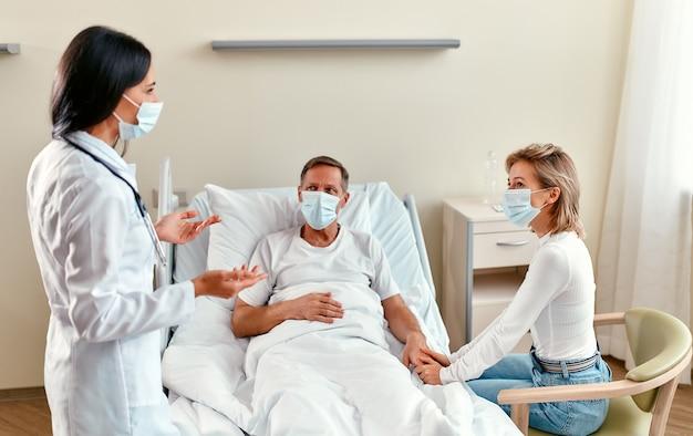 Una hermosa doctora con una máscara médica protectora se comunica con la familia de un paciente maduro que yace en una sala de un hospital moderno durante la epidemia de coronavirus o covid-19.