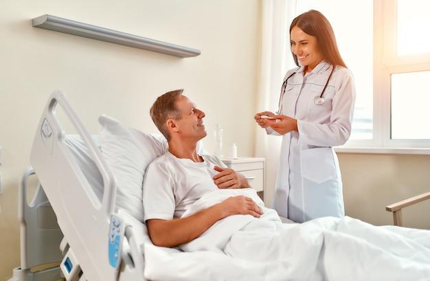 Una hermosa doctora mide la temperatura de un paciente masculino maduro que se encuentra en rehabilitación en una moderna sala de hospital.
