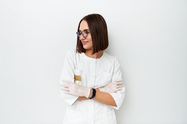 Hermosa doctora mirando a otro lado mientras posa en la cámara sobre fondo blanco con espacio de copia