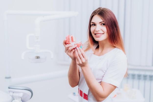 Hermosa doctora ortodoncista le muestra cómo cuidar sus dientes