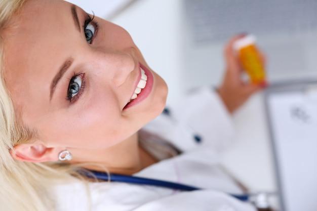 Hermosa doctora sonriente escribir receta