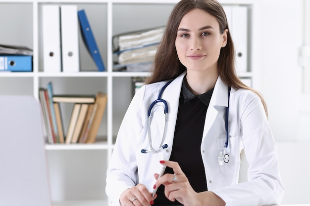 Hermosa doctora sonriente espera portapapeles