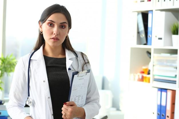 Hermosa doctora sonriente en retrato de lugar de trabajo