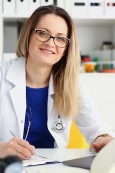 Hermosa doctora sonriente sentarse en el lugar de trabajo. visita de examen de ayuda al paciente de prevención física y de enfermedad 911 sala ronda prescribir remedio concepto de profesión de consultor de estilo de vida saludable