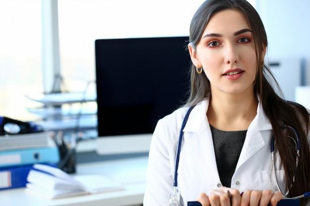 Hermosa doctora sonriente sentarse en el lugar de trabajo