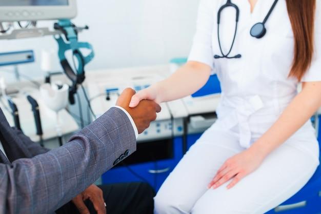 Una hermosa doctora sostiene la mano de la paciente asiática para animarla y simpatizarla y tocar su mano. el concepto de asociación, confianza y ética médica. malas noticias y apoyo.