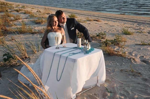 Hermosa elegante alegre joven pareja en la boda junto al mar d