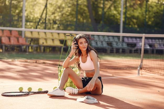 Hermosa y elegante chica en la cancha de tenis