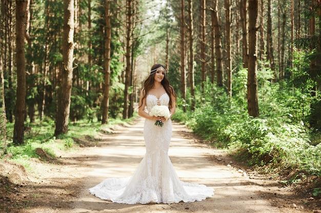 Hermosa y elegante chica modelo morena con peinado decorado con joyas en vestido de encaje de moda posando en el bosque temprano en la mañana