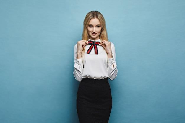 Hermosa y elegante chica modelo rubia sonriente en falda negra ajustando un lazo en su elegante blusa y posando en fondo azul en estudio