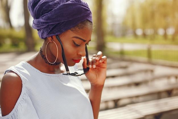 Una hermosa y elegante chica de piel oscura camina en una soleada ciudad veraniega
