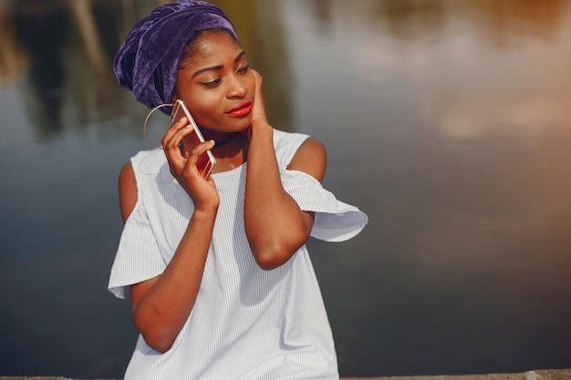 Una hermosa y elegante chica de piel oscura sentada en un soleado parque de verano cerca del agua