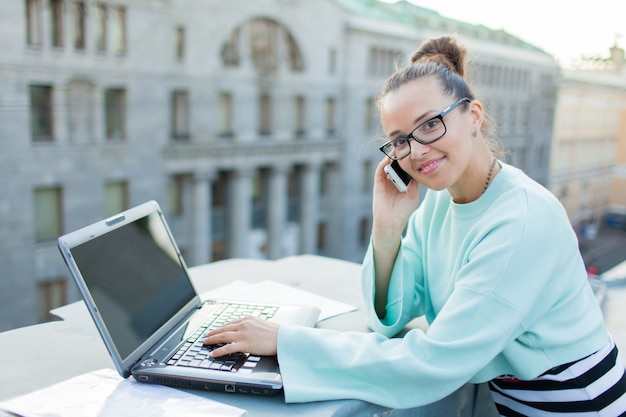Hermosa y elegante chica trabaja para una laptop.