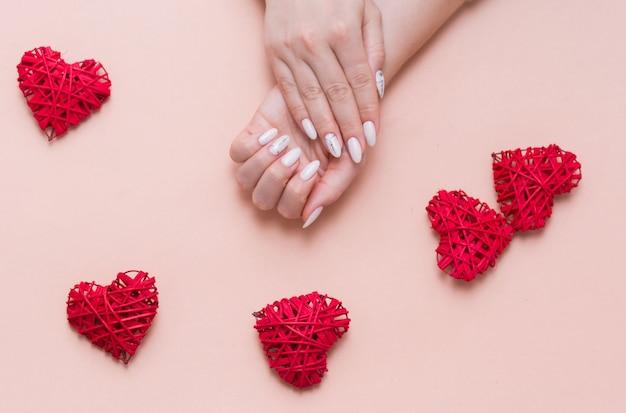 Hermosa y elegante manicura femenina sobre un fondo rosa con decoración de san valentín