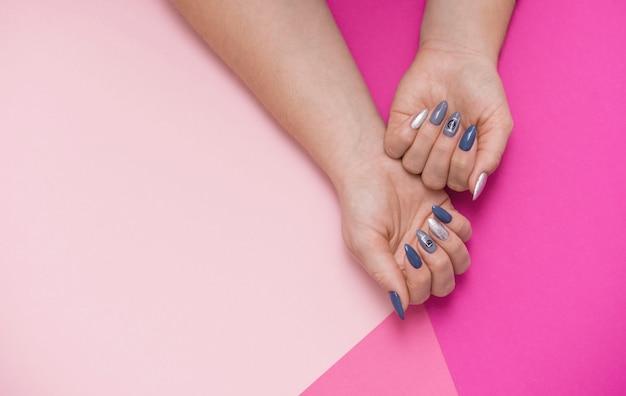 Hermosa elegante manicura femenina sobre un fondo rosa.
