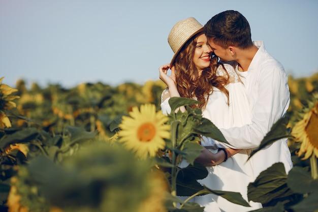Hermosa y elegante pareja en un campo con girasoles