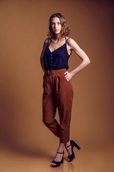 Hermosa y elegante señorita con maquillaje suave en pantalones beige de moda posando