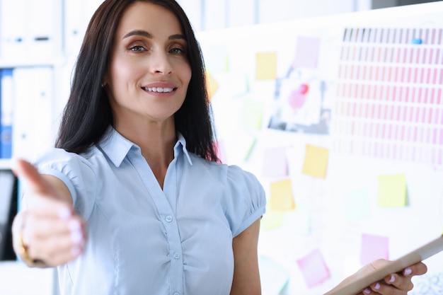 Hermosa empleada sonriente ofreciendo brazo al cliente