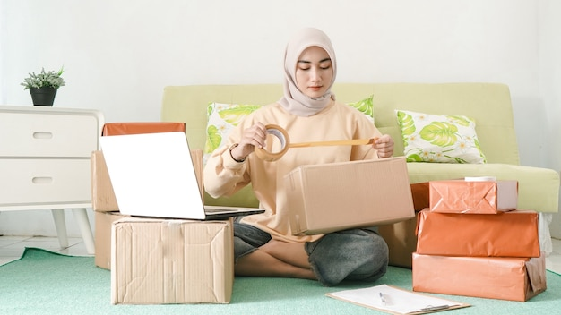Hermosa empresaria asiática embalaje pedidos de clientes en su habitación