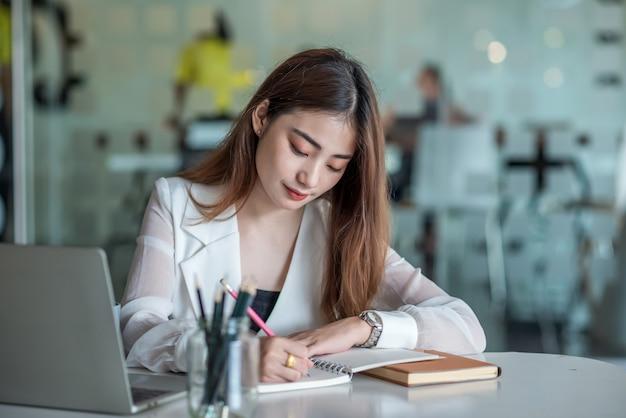 Hermosa empresaria asiática o gerente financiero que trabaja en la oficina moderna en la computadora portátil