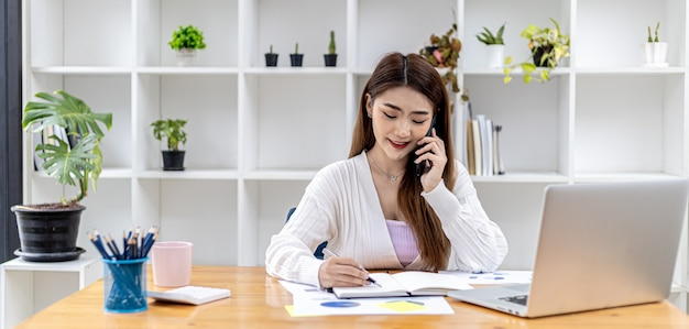 Hermosa empresaria asiática sentada en su habitación, hablando con su pareja a través del teléfono móvil y revisando documentos financieros, es una ejecutiva de una empresa de nueva creación. gestión financiera.