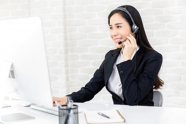 Hermosa empresaria asiática trabajando en call center como operadora
