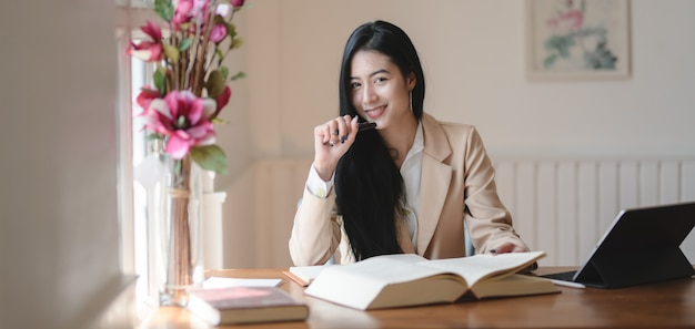 Hermosa empresaria asiática trabajando en su proyecto y sonriendo a la cámara