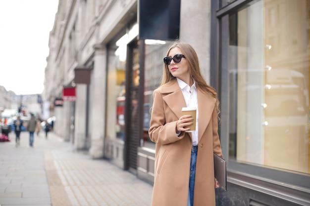 Hermosa empresaria blanca caminando en la calle con su computadora portátil y café