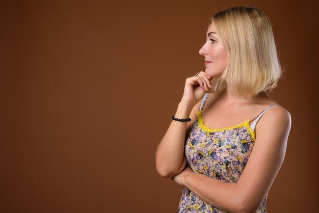 Hermosa empresaria con cabello corto y rubio contra la espalda marrón