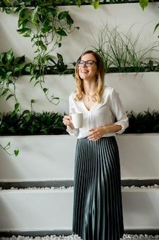 Hermosa empresaria caucásica de pie en su oficina por las plantas verdes y beber té