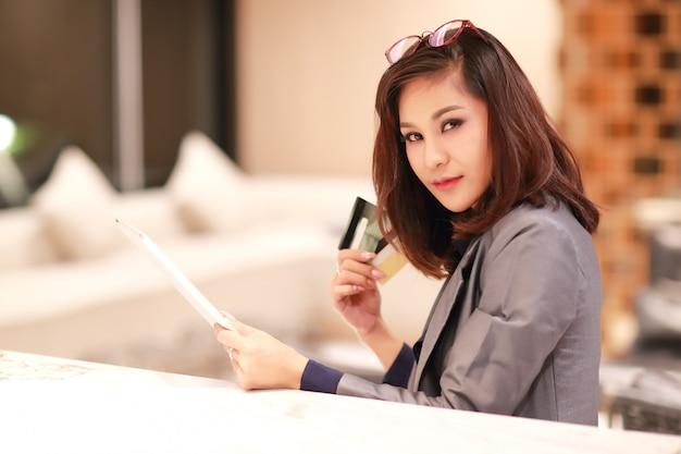 Hermosa empresaria de compras y pago en línea mediante el uso de tabletas y tarjetas de crédito disponibles