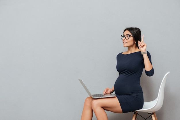 Hermosa empresaria embarazada tiene una idea usando laptop