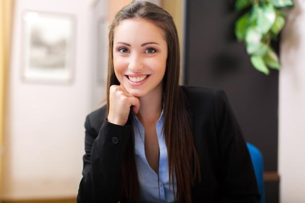 Hermosa empresaria joven sentado en su oficina