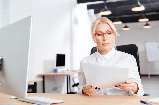 Hermosa empresaria madura pensativa leyendo papeles en office