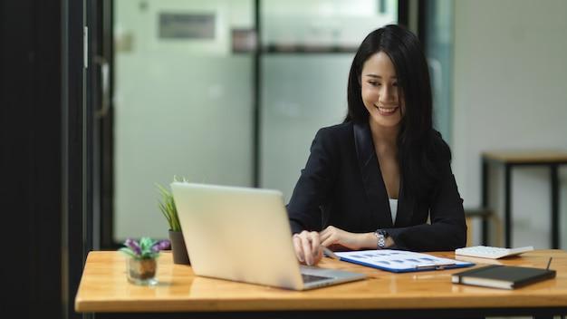 Hermosa empresaria mirando comprobar trabajar en un portátil con cara de sonrisa espacio de trabajo de oficina