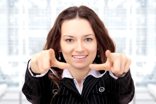 Hermosa empresaria muestra un dedo índice hacia adelante en la oficina.