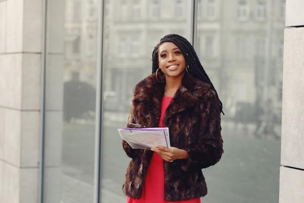 Hermosa empresaria negra en una ciudad de primavera