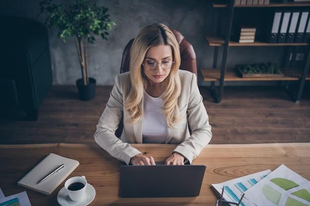 Hermosa empresaria rubia sentada en el escritorio con un portátil y un bloc de notas