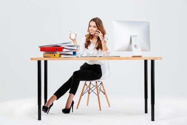 Hermosa empresaria sentada en el escritorio con un vaso de agua en la mano y hablando por teléfono isoltaed sobre el fondo blanco.