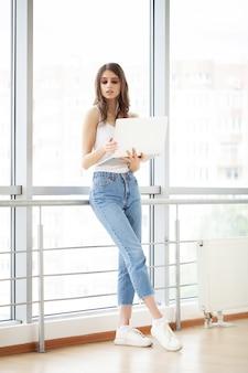 Hermosa empresaria trabajando en equipo portátil en la oficina moderna y luminosa.