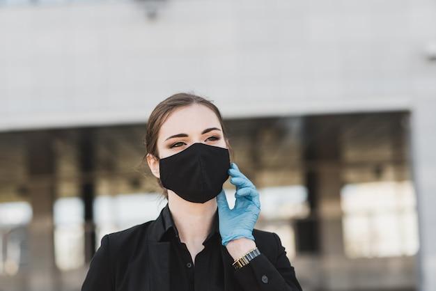 Hermosa empresaria en un traje negro en una máscara médica negra y guantes en la ciudad en cuarentena y aislamiento. pandemia covid-19. enfoque selectivo