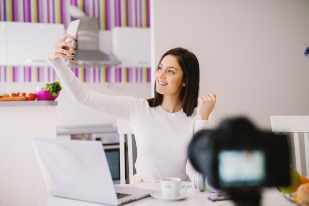 Hermosa y encantadora mujer joven está tomando una foto de sí misma con su teléfono frente a la cámara y la computadora portátil.